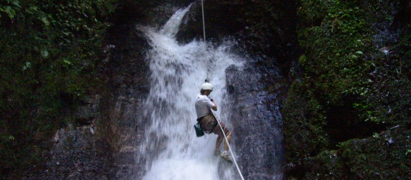 Rappelling down the front of a waterfall